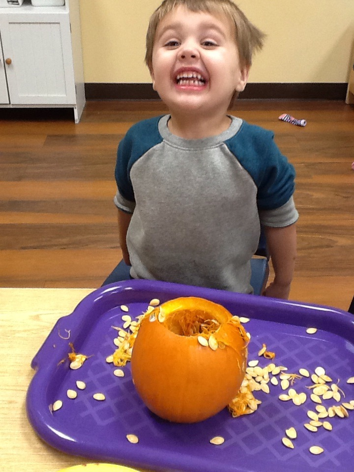 Henry is super smiling about pulling seeds from a pumpkin.