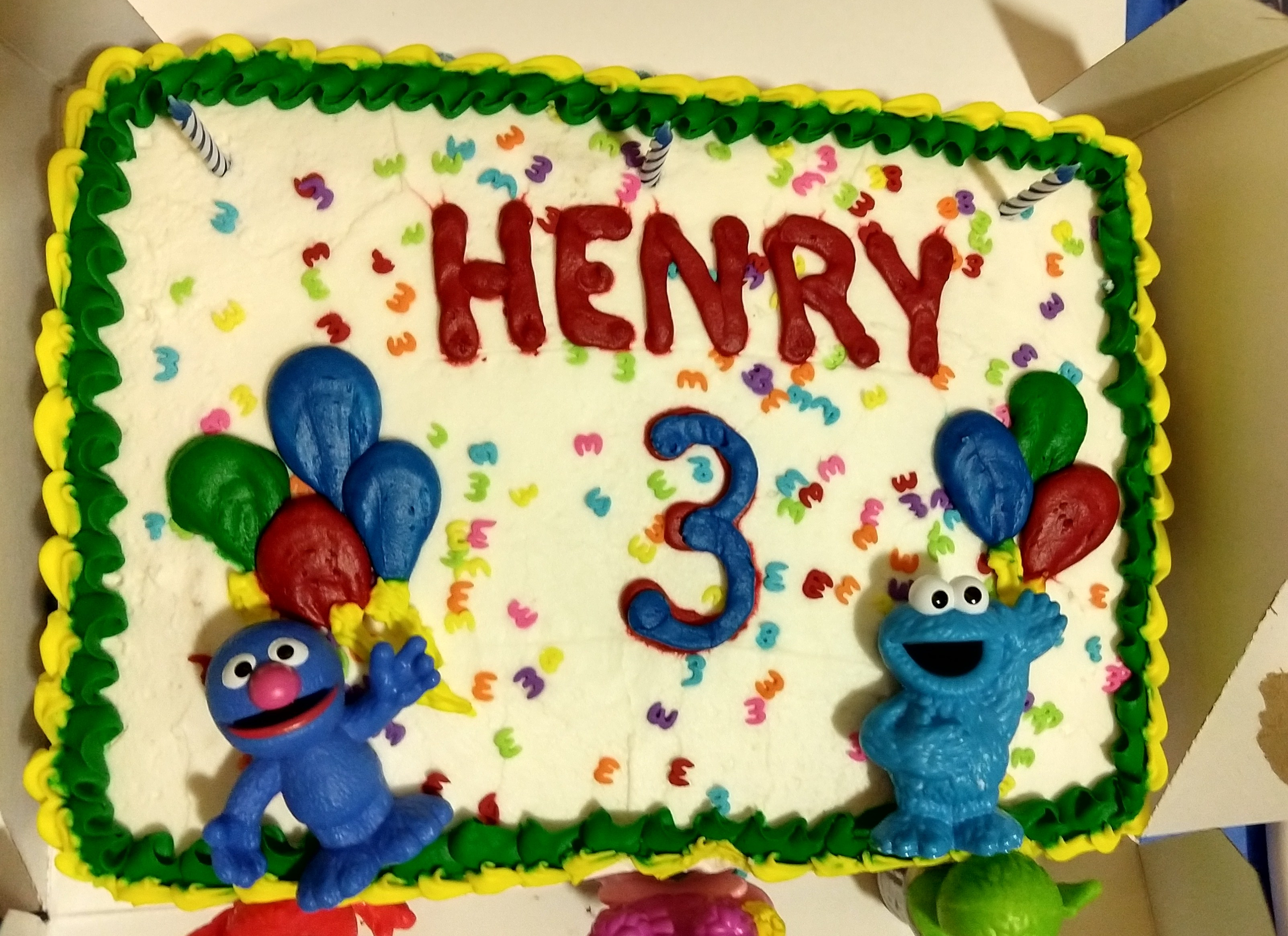 "A birthday cake with Grover and Cookie Monster. It says ""Henry"" and ""3."""
